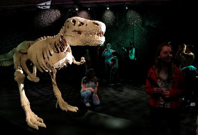Na snímke návštevníci si pozerajú skulptúru dinosaura zhotovenú z lega od amerického umelca Nathana Sawayu počas výstavy The Art of the Brick v Paríži