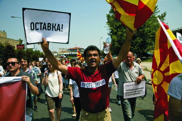 """Demonštrant drží transparent s nápisom """"Demisia"""" počas opozičného zhromaždenia v macedónskej metropole Skopje v nedeľu 17. mája 2015. Provizórny tábor v Skopje demonštranti postavili počas celonárodných protestov proti vláde konzervatívneho lídra Nikolu Gruevského, ktoré vyvrcholili v nedeľu zhromaždením za účasti 20.000 ľudí"""