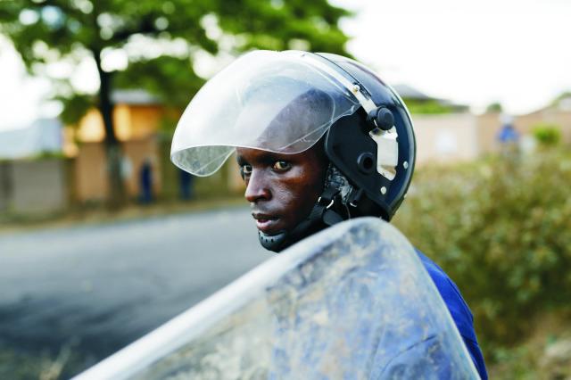 Policajt sleduje skupinu demonštrantov, ktorí hádžu kamene počas nepokojov v burundskej metropole Bujumbura