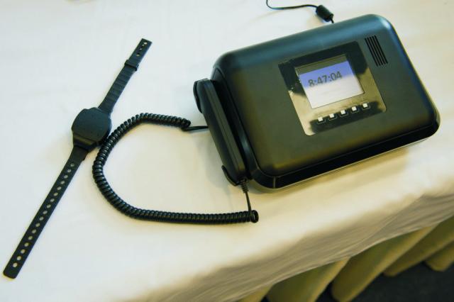 Na snímke náramok a domáca stanica na elektronický systém monitoringu osôb v praxi