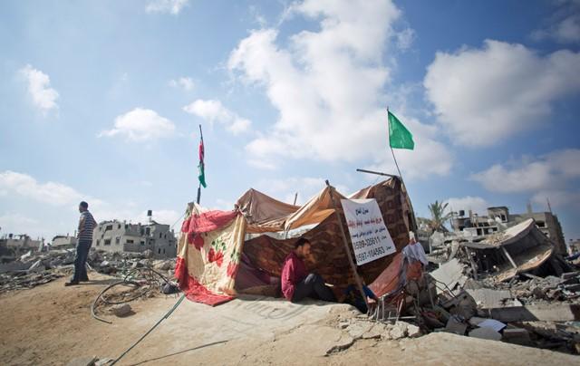 Na snímke Palestínčan sedí v provizórnom príbytku z dreva a plachiet pred zničeným domom v Šijaijáhu na predmestí Gazy