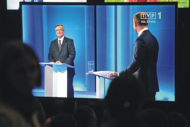 Ľudia sledujú prvú televíznu debatu medzi kandidátom opozičnej strany Právo a spravodlivosť (PiS) Andrzejom Dudom (vpravo) a súčasným prezidentom Bronislawom Komorowským 17. mája 2015 pred druhým kolom prezidentských volieb