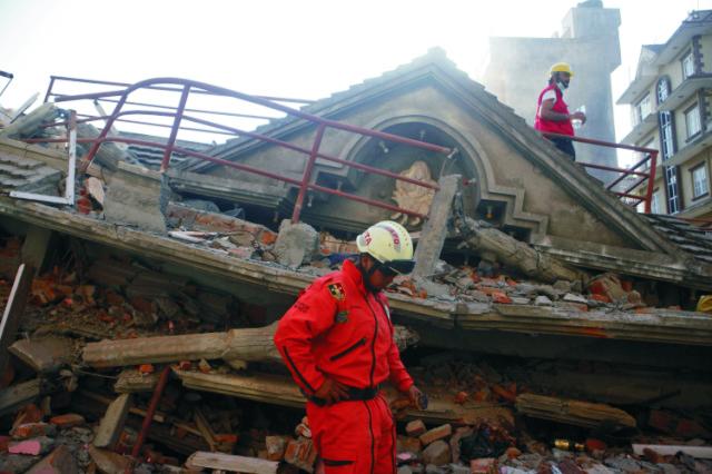 Na snímke záchranár stojí na mieste zrútenej budovy po ďalšom zemetrasení v nepálskom meste Káthmandu 12. mája 2015