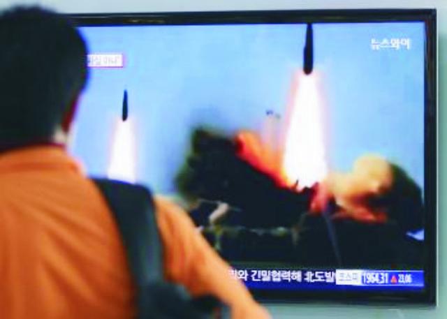 Na archívnej snímke muž sleduje na televíznej obrazovke odpálenie dvoch balastických rakiet stredného doletu, ktoré vypálila Severná Kórea do priestoru Japonského mora 26. marca 2014
