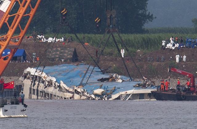 KK47 ien-li  - Na snímke obrátená výletná loï, ktorá sa potopila v rieke Jang-c'-iang v centrálnej èínskej provincii Hubej 5. júna 2015. Èínski záchranári obrátili výletnú úloï, ktorá sa v utorok 2. júna potopila v rieke Jang-c'-iang. Zo 460 cestujúcich sa podarilo zachráni 14 osôb. FOTO TASR/AP Rescuers use cranes to lift the capsized ship Eastern Star on the Yangtze River in Jianli county of southern China's Hubei province, as seen from across the river from Huarong county of southern China's Hunan province, Friday, June 5, 2015. The Eastern Star's top-deck cabins with smashed blue roofs jutted out of gray water Friday after Chinese disaster teams righted the capsized river cruiser to ease the search for people still missing. (AP Photo/Andy Wong)