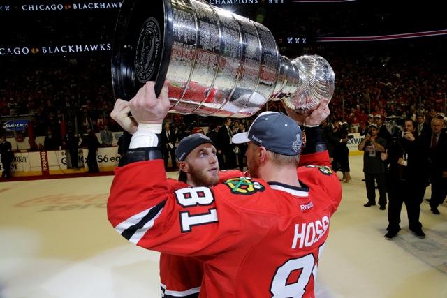 Na snímke hráč Chicaga Blackhawks Patrick Kane predáva Stanleyho pohár Slovákovi Mariánovi Hossovi