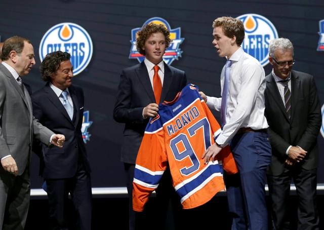 Na snímke kanadský hokejista Connor McDavid si oblieka dres Edmontonu