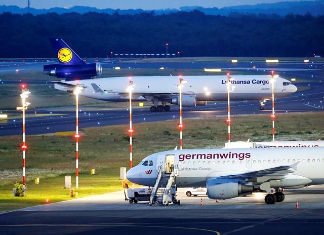 Na snímke lietadlo (hore) s pozostatkami niekoľkých obetí leteckého nešťastia pristálo na letisku v  nemeckom Düsseldorfe