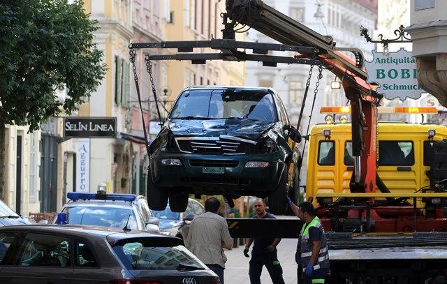 Na snímke odvážanie terénneho vozidla, ktorého vodič vrazil do davu ľudí z miesta nehody v centre Grazu