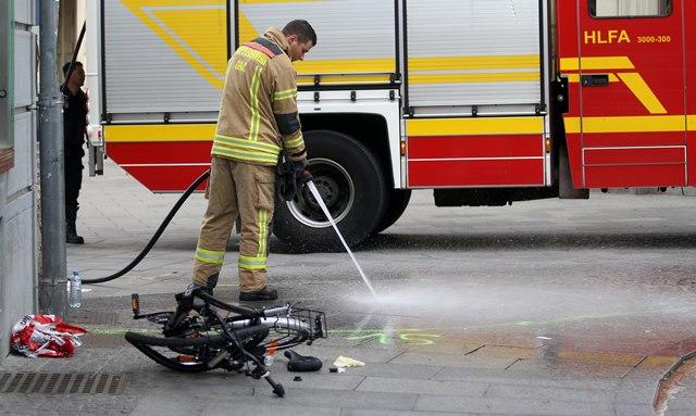 Na snímke hasič čistí ulicu od krvi pri zničenom bicykli na mieste nehody, kde vodič terénneho vozidla vrazil do davu ľudí v centre Grazu