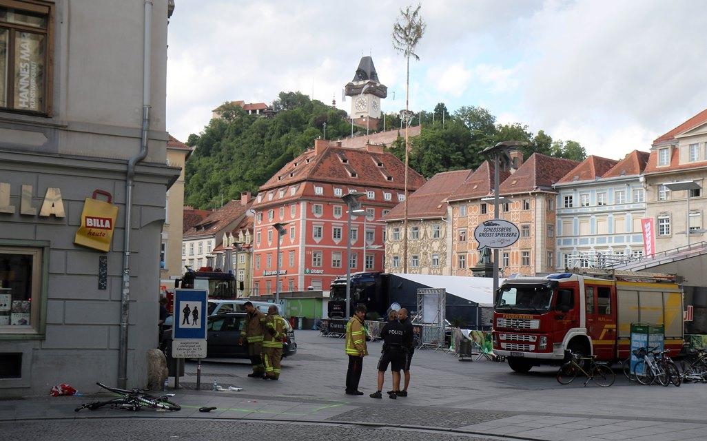 Na snímke hasiči a policajti stoja pri zničenom bicykli na mieste nehody, kde vodič terénneho vozidla vrazil do davu ľudí v centre Grazu