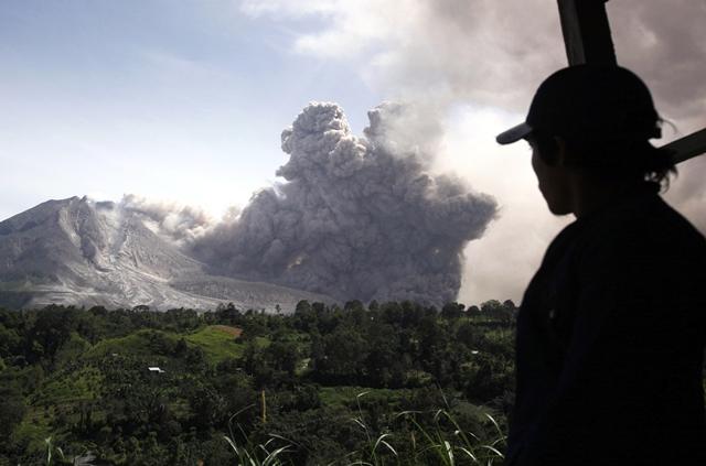 Na snímke muž sa pozerá na indonézsku sopku Sinabung