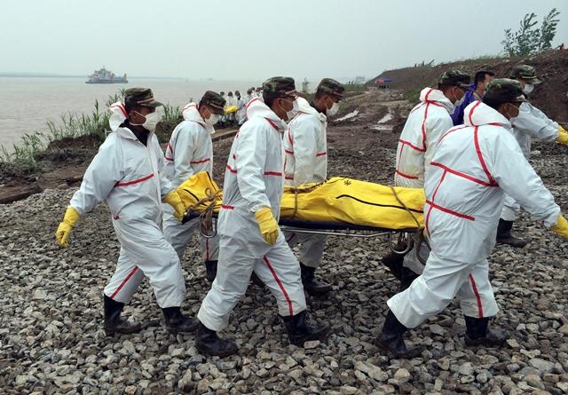 Na snímke čínski záchranári nesú telo obete z potopenej lode v rieke Jang-c'-ťiang