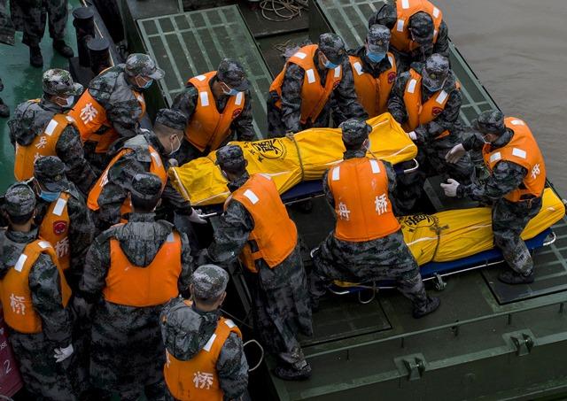 Na snímke záchranári vyťahujú mŕtve telo z prevrátenej výletnej lode