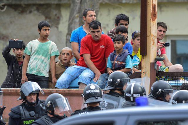 Na snímke migranti sledujú policajtov, ktorí strážia vchod do tábora v Debrecíne