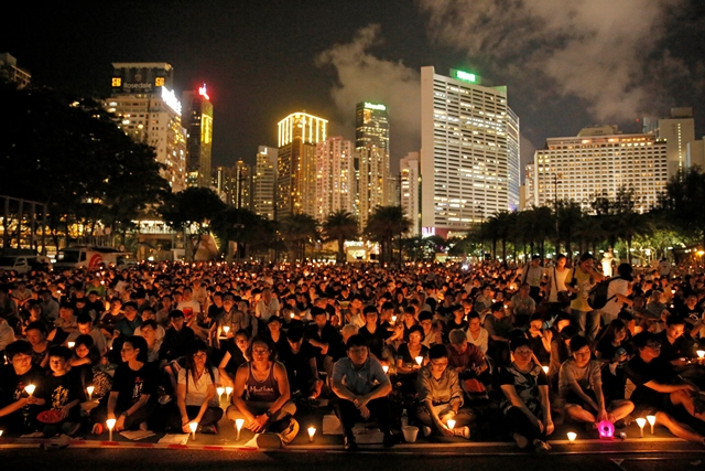 Na snímke desaťtisíce ľudí sa v Hongkongu zúčastnili na tichej sviečkovej demonštrácii v parku v centre na pamiatku 26. výročia krvavého vojenského potlačenia demonštrantov na pekinskom Námestí nebeského pokoja