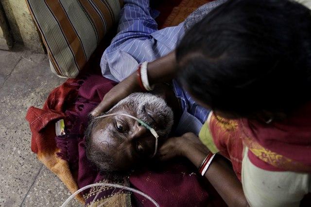 Na snímke žena (vpravo) sedí vedľa svojho manžela , ktorý leží po konzumácii nelegálne vyrobeného alkoholu v nemocnici v indickom Diamond Harbour