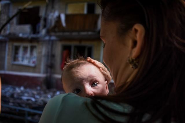 Na snímke žena drží v náručí svoje bábätko pred bytovkou zničenou ostreľovaním v obci Horlivka, ktorá leží severne od mesta Doneck