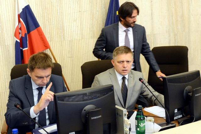 Na snímke zľava podpredseda vlády a minister financií SR Peter Kažimír, predseda vlády SR Robert Fico (sediaci) a podpredseda vlády a minister vnútra SR Robert Kaliňák
