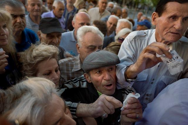 Na snímke dôchodcovia sa tlačia v rade a čakajú na lístky s poradovými číslami pred bankou v Aténach