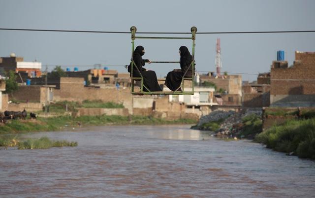 Na snímke pakistanské ženy sa prepravujú cez rozvodnenú rieku na lanovke v pakistanskom meste Ráwalpindí