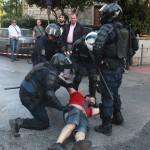 Na snímke príslušníci gréckych poriadkových síl zatýkajú demonštranta počas zrážok na zhromaždení proti reformám a úsporným opatreniam, ktoré požadujú veritelia