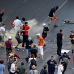 Na snímke príslušníci gréckych poriadkových síl hádžu kanister so slzotvorným plynom na demonštrantov počas zrážok na zhromaždení proti reformám a úsporným opatreniam, ktoré požadujú veritelia
