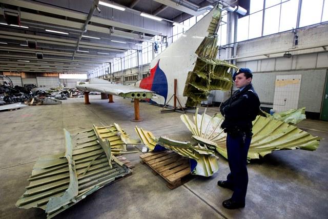 Na snímke holandský vojenský policajt stojí pri troskách lietadla Boeing 777 letu MH 17 Malazijských aerolínii v hangári na leteckej základni Gilze Rijen v Holandsku