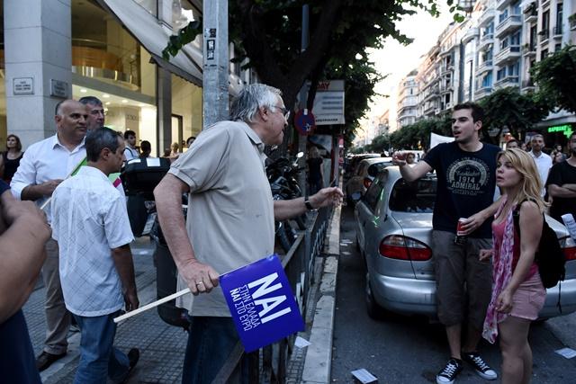Na snímke grécky demonštrant (vľavo) podporujúci reformy a úsporné opatrenia, ktoré požadujú veritelia argumentuje s párom, ktorý zastáva opačný názor v nadchádzajúcom referende počas zhromaždenia v gréckom prístavnom meste Thessaloniki