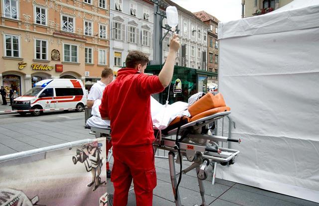 Na snímke záchranári odvážajú na nosidlách zraneného človeka na mieste nehody, kde vodič terénneho vozidla vrazil do davu ľudí v centre Grazu
