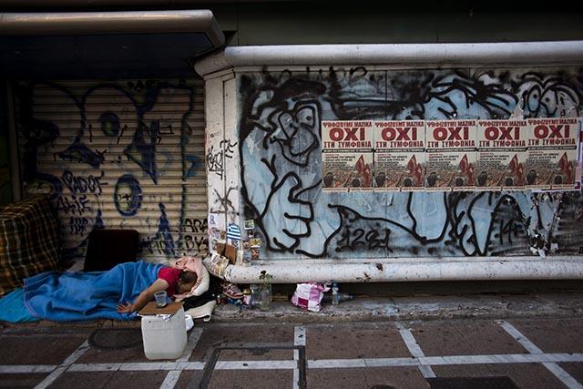 Na snímke bezdomovec spí pri zavretom obchode oblepenom plagátmi s nápisom NIE po referende v centre Atén.