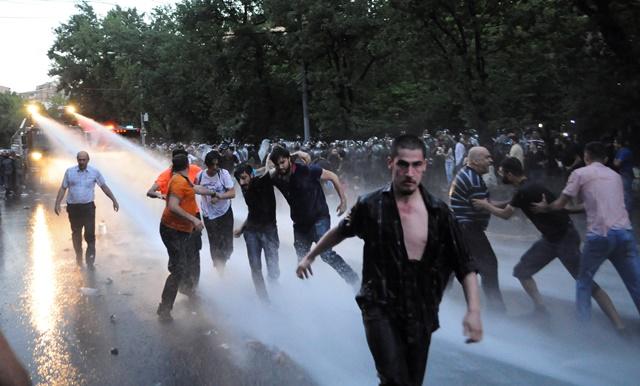 Na snímke arménska polícia rozháňa demonštrantov vodnými delami v arménskom Jerevane