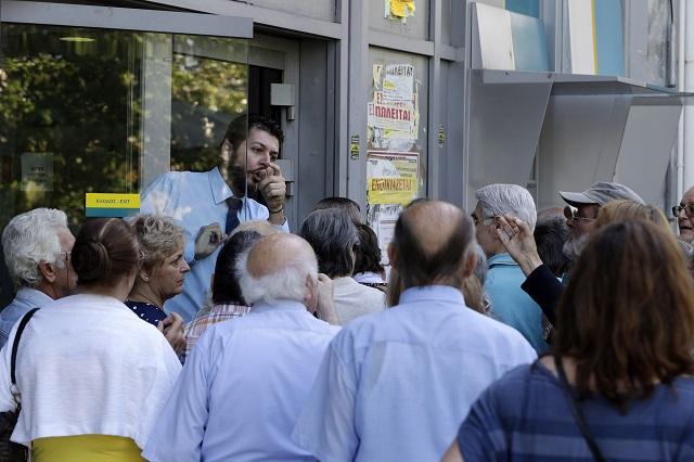 Na snímke zamestnanec banky informuje dôchodcov počas otvorenia pobočky  v Aténach