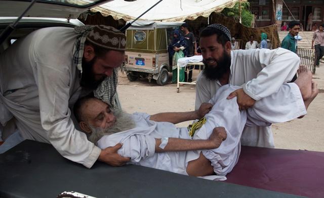 Na snímke rodinní príslušníci nesú starého muža s úpalom do nemocnice v pakistanskej metropole Karáči