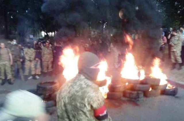 Na snímke demonštranti a horiace pneumatiky počas protestu