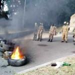 Na snímke demonštranti stoja a sledujú horiace pneumatiky
