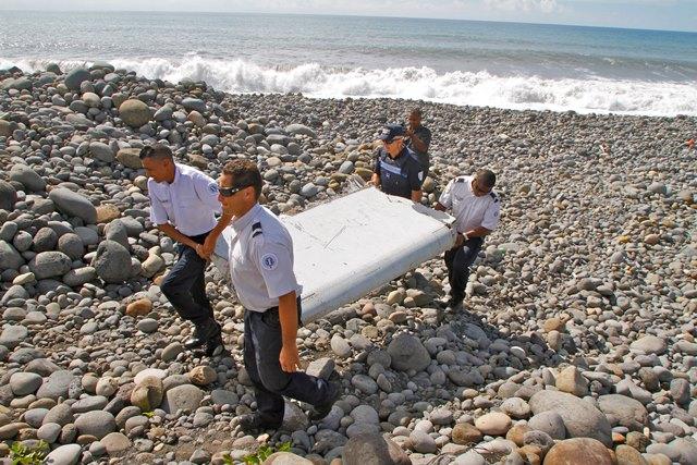 Na snímke policajti nesú časť lietadla