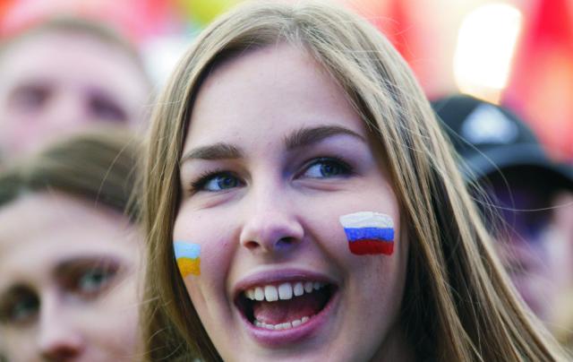 Na archívnej snímke dievča s ruskou a ukrajinskou vlajkou namaľovanou na lícach prichádza na koncert pri príležitosti prvého výročia referenda, na základe ktorého sa ukrajinský polostrov Krym stal súčasťou Ruskej federácie v centre Moskvy na Červenom námestí