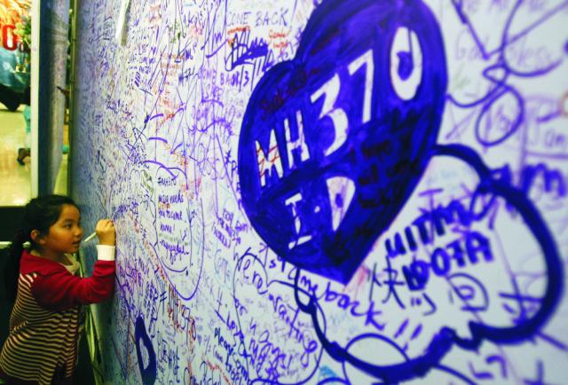 Na archívnej snímke dievča píše odkaz pre pasažierov nezvestného letu Malajzijských aerolínií MH370 v obchodnom centre v malajzijskom meste Petaling Jaya pri Kuala Lumpure