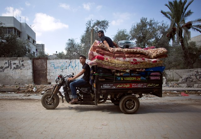 Na snímke  Palestínčania sa so svojimi vecami vracajú na motobicykli späť do svojich príbytkov v Šijaijáhu na predmestí Gazy, v severnej časti pásma Gazy