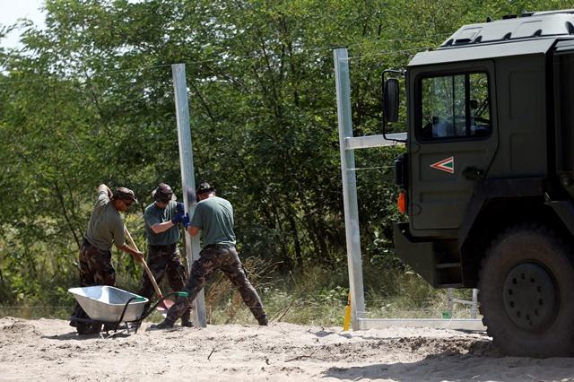 Na snímke príslušníci maďarských obranných síl počas výstavby dočasných zábran na maďarsko-srbských hraniciach