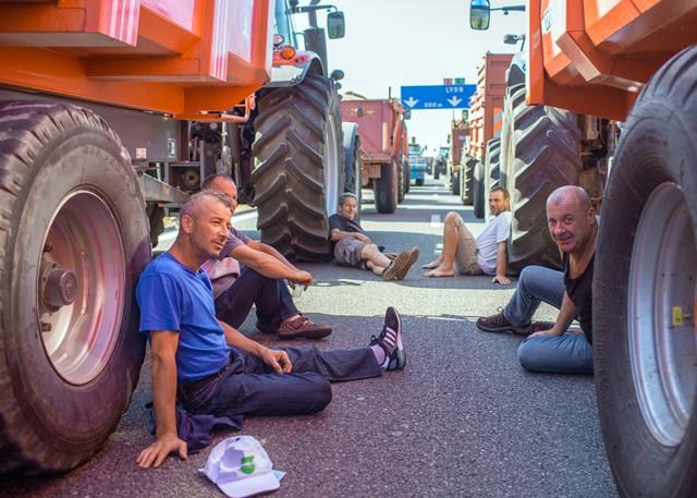 Na snímke francúzski poľnohospodári sedia v chládku vedľa traktorov a blokujú diaľnicu z Paríža do Lyonu v Limoneste pri Lyone v strednom Francúzsku počas pokračujúcich protestov