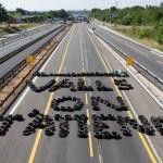 """Na snímke francúzski poľnohospodári  vytvorili z pneumatík nápis a odkaz pre francúzskeho premuíra Manuela Vallsa : """"Valls, čakáme na Teba"""", ktorým blokujú diaľnicu"""