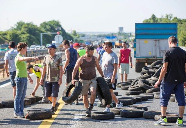 Na snímke francúzski poľnohospodári blokujú pneumatikami diaľnicu z Paríža do Lyonu v Limoneste pri Lyone