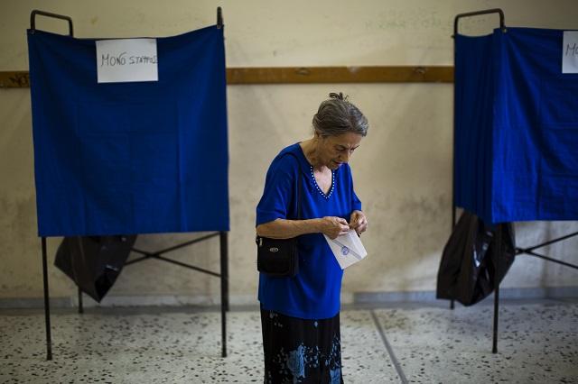 Na snímke žena vo volebnej miestnosti v Aténach