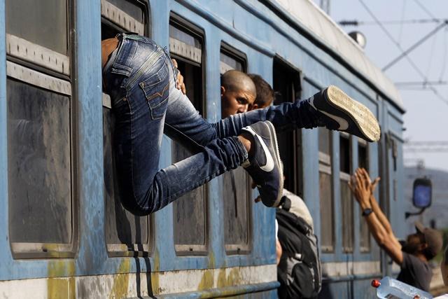 Na snímke migrant sa snaží dostať cez okno do vlaku