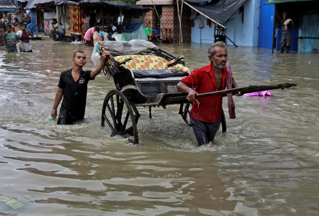 Na snímke indický rikšiar prechádza cez zaplavenú ulicu v indickom meste Kalkata