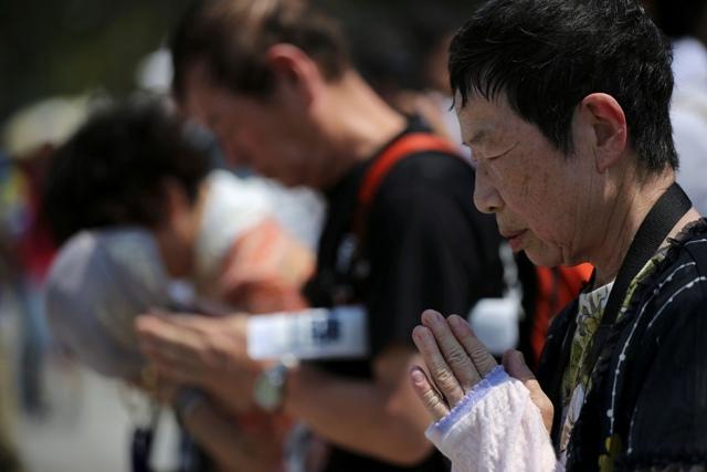 Na snímke návštevníci sa modlia za obete atómovej bomby