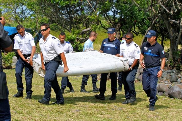 Na snímke policajti nesú časť lietadla. Ilustračné foto