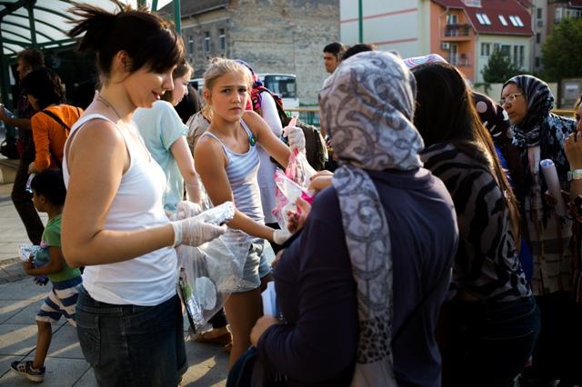 Na snímke dobrovoľníci dávajú migrantom jedlo a vodu v Segedíne
